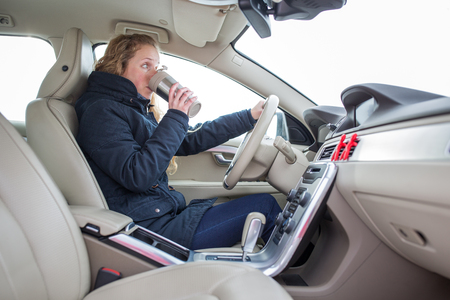 Woman driving a car - female driver at a wheel of a modern car, drinking her morning coffee (shallow DOF; color toned image) photo