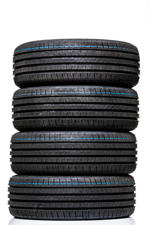 Stack of brand new high performance car tires on clean high-key white studio background Stock Photo