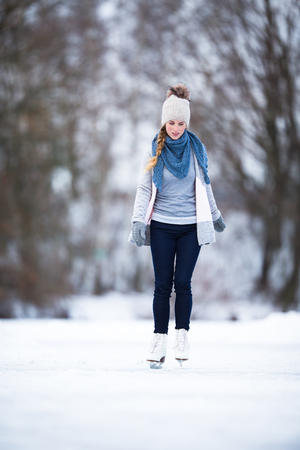 Young woman ice skating outdoors on a pond on a freezing winter day (color toned image; motion blurred image) photo
