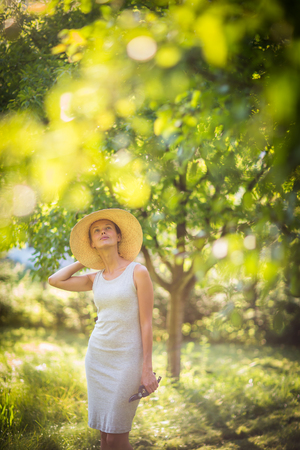 grass cutting: Pretty, young woman gardening in her garden, cutting branches, taking care of the fruit trees in her lovely orchard