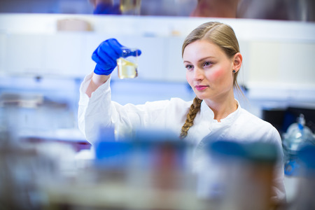 Portrait of a female researcher carrying out research in a chemistry lab (color toned image; shallow DOF) Фото со стока
