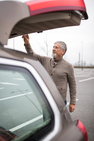 rev: Senior man by his car, closing the trunk lid in a mall parking lot, going shopping (color toned image; shallow DOF)