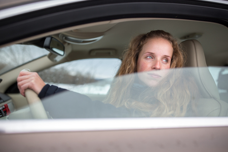 Pretty young woman driving her new car (shallow DOF; color toned image) photo