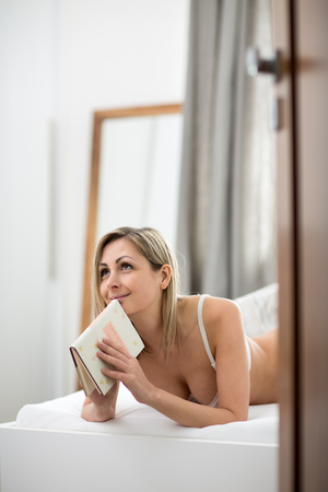 Beautiful young woman in bed, reading her favorite book (shallow DOF, color toned image) photo