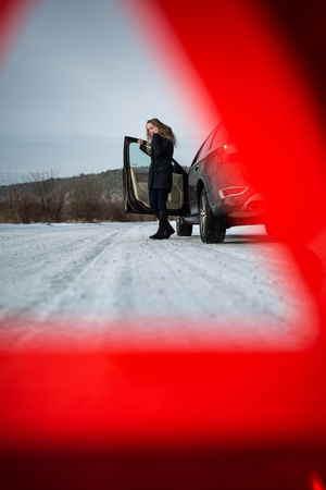 Young woman setting up a warning triangle and calling for assistance after her car broke down in the middle of nowhere on a freezing winter day Stock Photo - 78363669