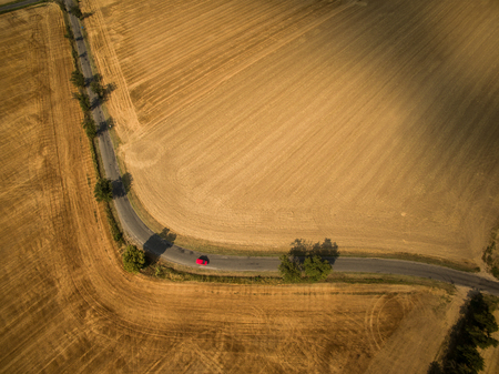 Aerial view of a country road amid fields with a red car Stock Photo