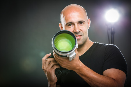 Young, pro male photographer in his studio during a photo shoot (color toned image; shallow DOF)