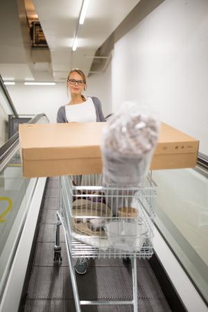 Mooie, jonge vrouw die het juiste meubilair kiest voor haar appartement in een moderne winkel voor woonaccessoires - met een trolley, klaar winkelen, de winkel verlaten, naar huis gaan met de gekochte goederen (kleurafbeeldingen, ondiepe DOF)