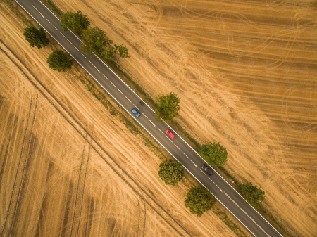 Aerial view of a country road amid fields with a car on it Stock Photo - 78397944