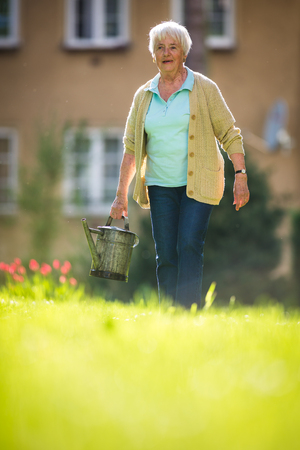 Senior woman doing some gardening in her lovely garden Imagens