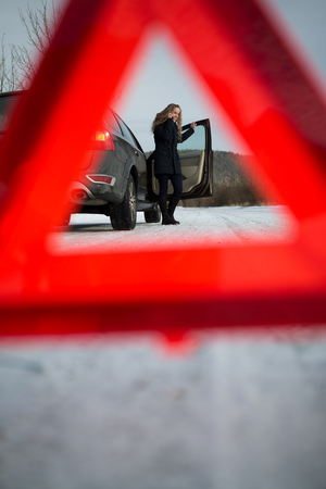 Young woman setting up a warning triangle and calling for assistance after her car broke down in the middle of nowhere on a freezing winter day