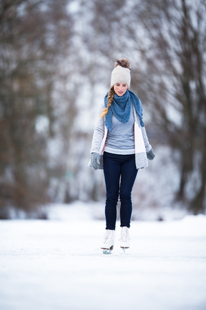 Young woman ice skating outdoors on a pond on a freezing winter day (color toned image; motion blurred image) Stock Photo