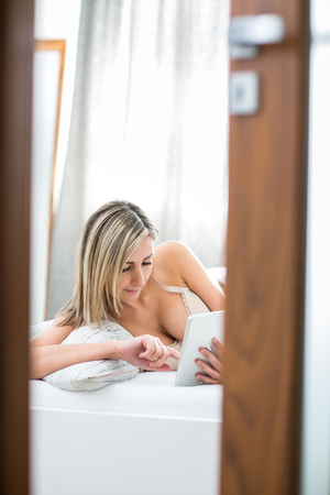 wellness sleepy: Beautiful young woman in bed, using her tablet computer first thing in the morning Stock Photo