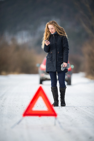 Young woman setting up a warning triangle and calling for assistance after her car broke down in the middle of nowhere on a freezing winter day Stock Photo - 78364883