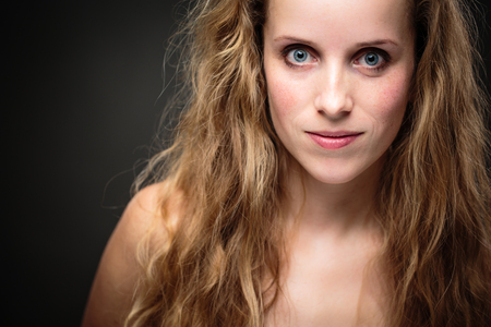 Studio glamour portrait of a pretty, young woman with lovely curly hair photo