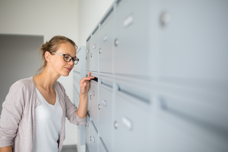 Pretty, young woman checking her mailbox for new letters 版權商用圖片 - 80899074
