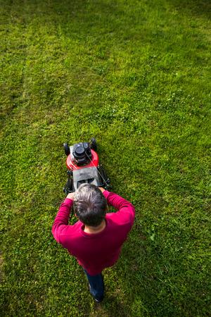 Senior Mann den Rasen in seinem Garten zu mähen Standard-Bild - 80925935