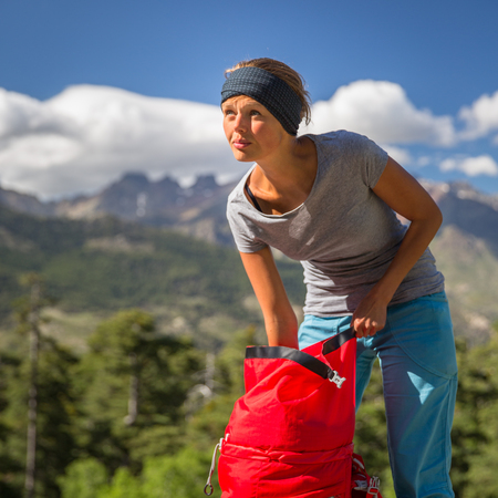 woman sandals: Pretty, female hiker in high mountains packing her backpack