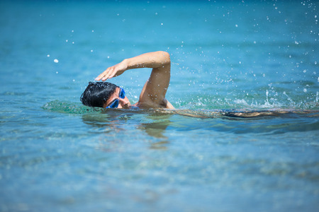 Young man swimming the front crawl in the sea (swimmer, triathlon) photo