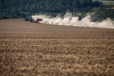 乾燥した農場フィールドを耕しトラクター