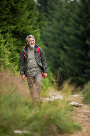 Active senior hiking in high mountains - enjoying his retirement in an active way photo