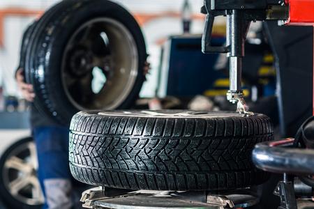 Dentro de un garaje - moderno coche esperando a que el mecánico para cambiar sus ruedas / neumáticos (DOF superficial, imagen a color entonado)