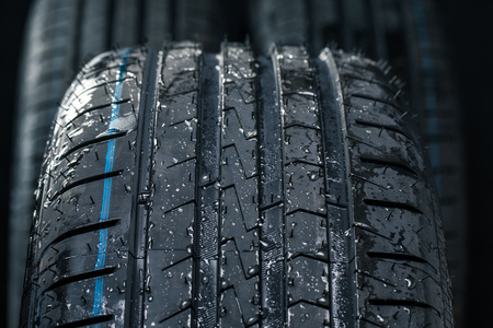 Stack of brand new high performance car tires on clean high-key white studio background Stock fotó