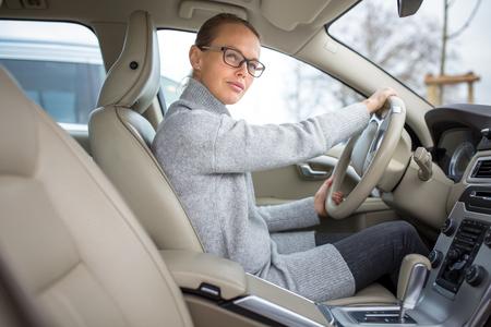 여자 운전 -, 현대 자동차의 바퀴에서 여성 운전자를 편안한 미소 미소, 행복을 찾고 (얕은 DOF; 톤 컬러 이미지)