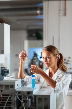 Portrait d'une femme chercheur faire de la recherche dans un laboratoire, en utilisant un ordinateur tablette pour la collecte de données et la visualisation (DOF peu profonde, image couleur tonique)