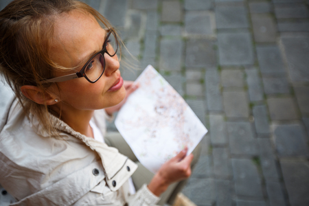 Female tourist with a map discovering a foreign city (shallow DOF; color toned image)