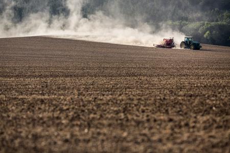 Tractor plowing a dry farm field Stok Fotoğraf - 85687117