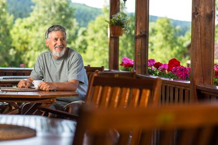 Un bel homme de grande taille qui profite de son café du matin sur une terrasse de l'hôtel de montagne pendant ses vacances