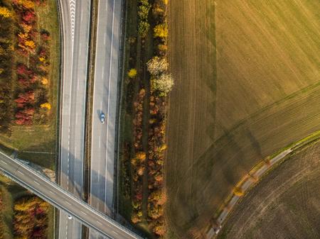 Vue aérienne d'une route au milieu des champs avec des voitures sur elle