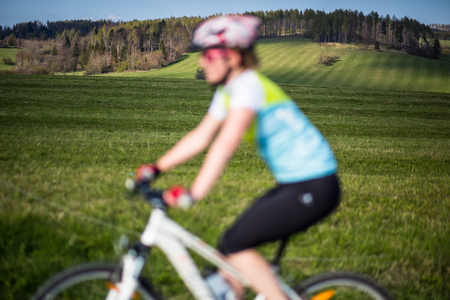 Female mountain biker out of focus with in focus landscape in the distance behind her Banque d'images