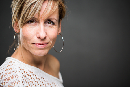 Portrait of a smiling middle aged caucasian woman against grey background (shallow DOF; color toned image) Banque d'images