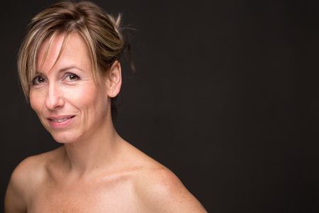 Portrait of a smiling middle aged caucasian woman against dark background - radiating confidence and femininity Banque d'images