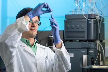 Chercheur masculin senior effectuant des recherches scientifiques dans un laboratoire (DOF peu profond, image tonifiée en couleur)