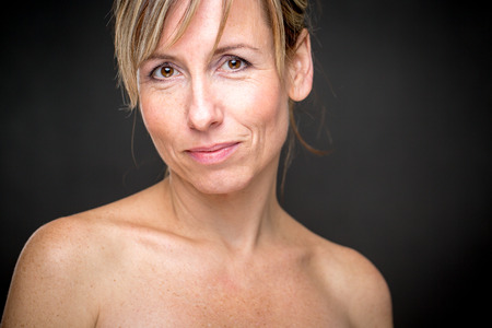 Portrait of a smiling middle aged caucasian woman against dark background - radiating confidence and femininity Lizenzfreie Bilder