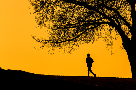 Silhouette of a  young man running outdoors on a lovely sunny evening