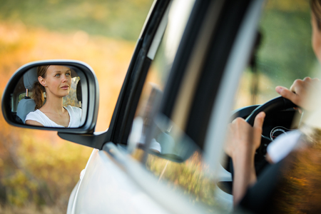 Pretty, young woman  driving her car - reflection in the side mirror
