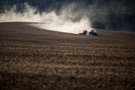 Tractor plowing a dry farm field Stok Fotoğraf - 85708794