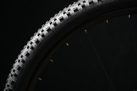 Modern MTB race mountain bike tyre isolated on black background in a studio Lizenzfreie Bilder