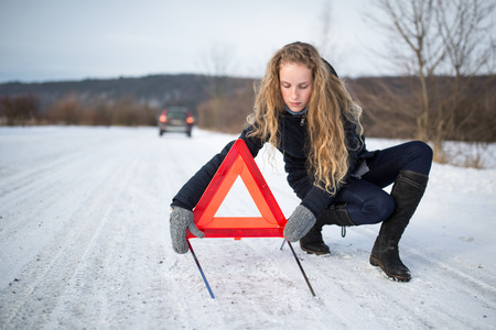 Young woman setting up a warning triangle and calling for assistance after her car broke down in the middle of nowhere on a freezing winter day Stock Photo - 85661202