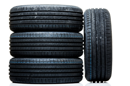 Stack of brand new high performance car tires on clean high-key white studio background Banco de Imagens