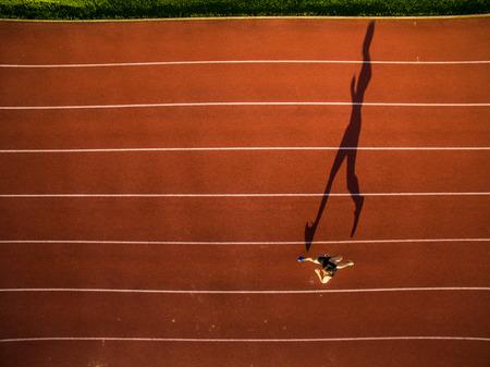 Plan d'un jeune athlète masculin s'entraînant sur une piste de course. Sprinter en cours d'exécution sur les pistes d'athlétisme vu d'en haut
