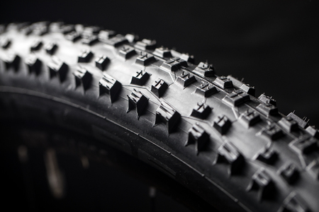 Modern MTB race mountain bike tyre isolated on black background in a studio 版權商用圖片