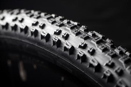 Pneu de vélo de montagne moderne MTB course isolé sur fond noir dans un studio
