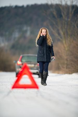 젊은 여자가 경고 삼각형을 설정하고 그녀의 차가 아무데도의 한가운데에 동결 겨울 날에 고장 후 도움을 요청 스톡 콘텐츠
