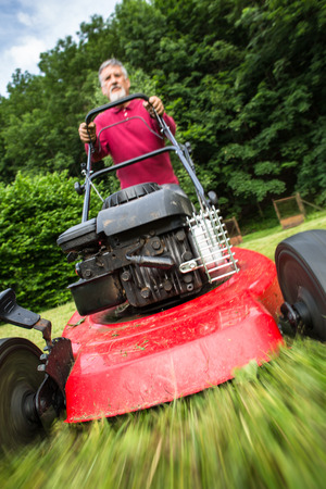 Älterer Mann, der den Rasen in seinem Garten mäht (selektiver Fokus; flacher DOF)
