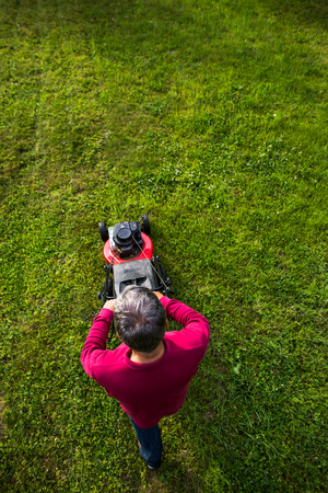 Lterer Mann , der den Rasen in seinem Garten mähen Standard-Bild - 93024843